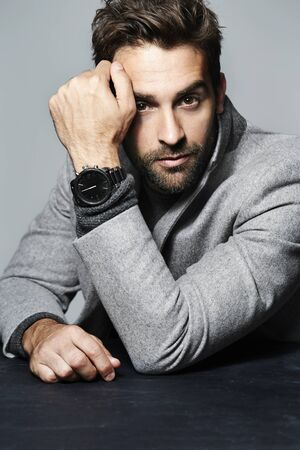 Intense dude in smart suit with watch Stock Photo