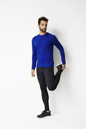 Stretching man in sportswear, studio
