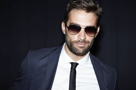 smirking: Smirking man in suit and shades, portrait