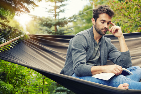 Man relaxing on hammock with book Standard-Bild