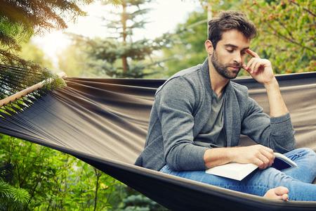 Man relaxing on hammock with book Standard-Bild