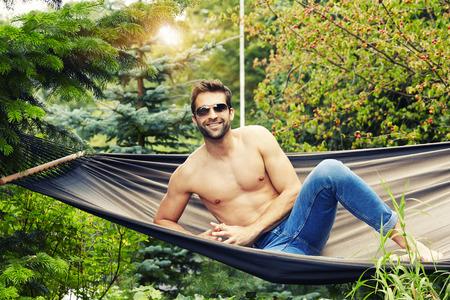 Shirtless dude in hammock looking at camera, smiling