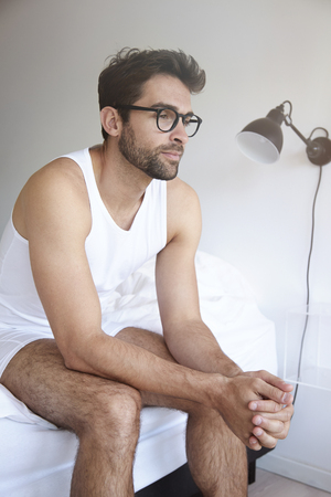 Man sitting on edge of bed, looking away