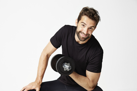 Smiley guy lifting weight in studio, portrait Stock Photo