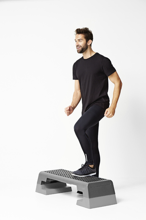 stepping: Man stepping on exercise step, studio Stock Photo