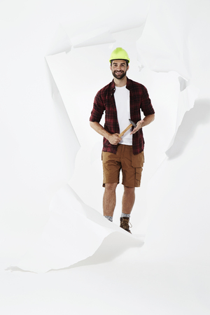 undone: Happy builder with hammer emerging through torn page