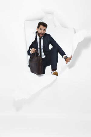 escaping: Businessman escaping from torn paper, portrait