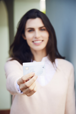 contactless: Woman holding credit card in focus Stock Photo