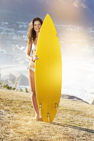 Sunlit surfer girl standing with board, smiling