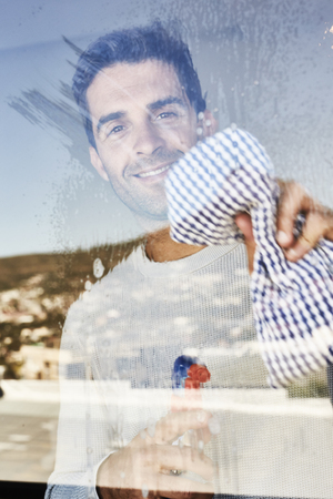 House husband cleaning windows, portrait Stock Photo