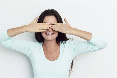 Beautiful woman covering eyes in studio Stock Photo