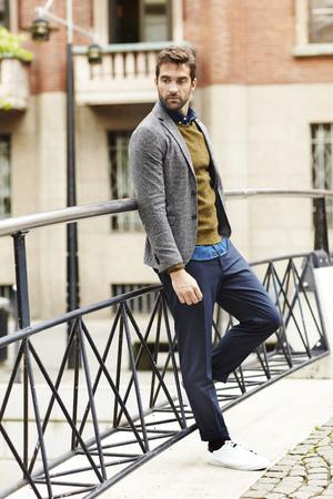 Fashionable fellow standing on bridge Stock Photo