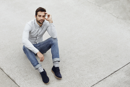 Jeans and shirt dude sitting on ground Stock Photo