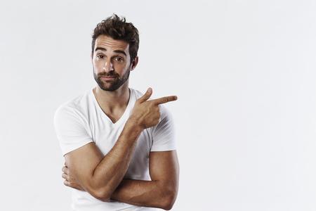 Dude pointing in white studio, portrait