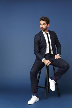 Businessman sitting on stool in blue studio