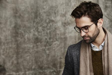 안경과 스카프를 입은 사려 깊은 남자