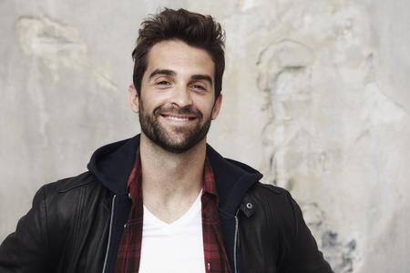 undone: Smiling stubble man in leather jacket, portrait Stock Photo