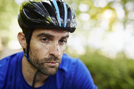 Mud spattered man in cycling helmet