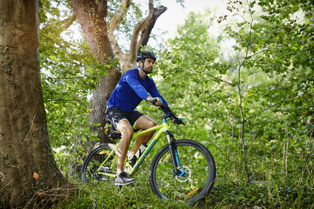 Man cycling on bike in forest Stock Photo