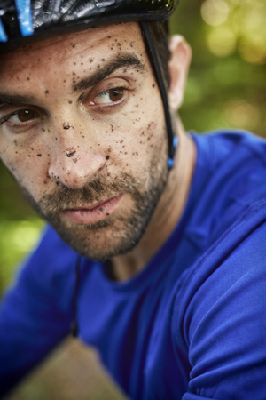 spattered: Dirty guy on bike, looking away