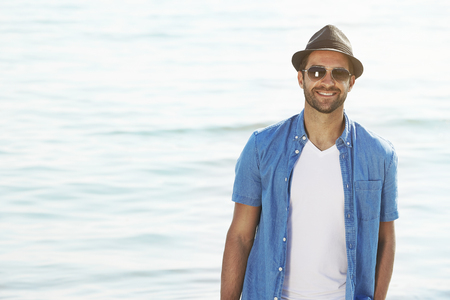 undone: Dude in hat and shades smiling at the sea