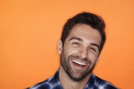 Laughing man in orange studio, portrait