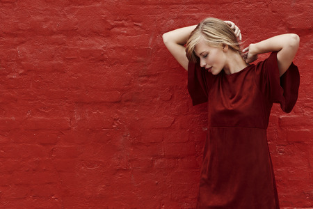 Red dress beauty against red wall