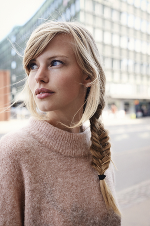 Blue eyed girl in city, looking away