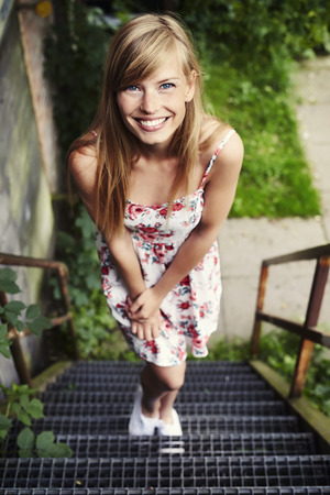 Beautiful woman in floral dress on steps