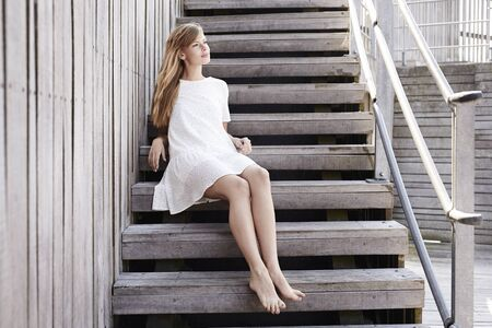Barefoot beauty sitting on steps, smiling