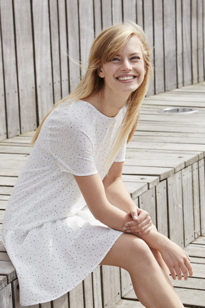 Beautiful smiling woman in white dress Stock Photo