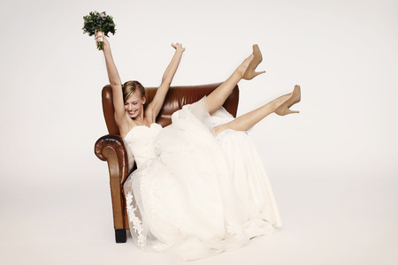 Excitable bride in armchair, cheering Stock Photo