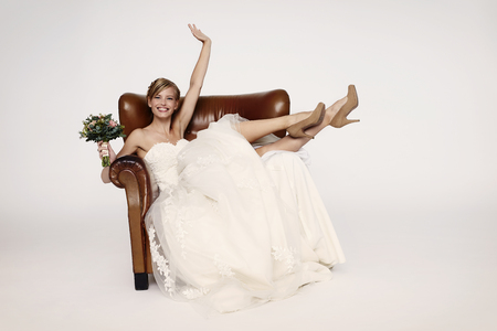 Bride in armchair smiling at camera Stock Photo