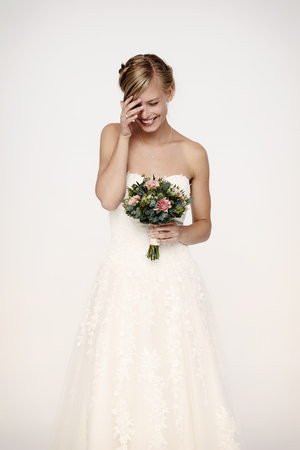 Laughing bride in white dress with flowers