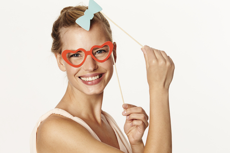 Beautiful woman holding bow tie and glasses disguise Stock Photo