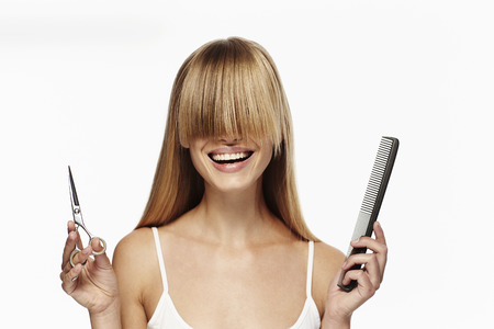Blonde haired woman with long fringe and scissors Stock Photo