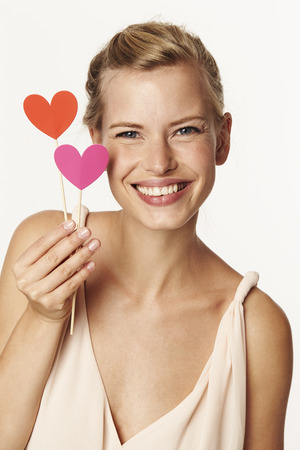 Beautiful woman holding love hearts, smiling