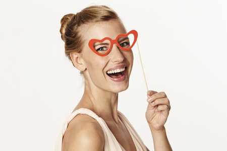 Woman laughing in heart shaped spectacles, portrait