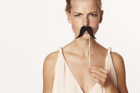 Beautiful blond holding mustache disguise, portrait