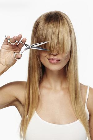 Scissor girl à couper les longs cheveux blonds, studio Banque d'images - 75817770