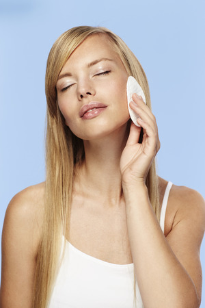 Gorgeous woman cleansing skin, eyes closed Stock Photo