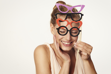 Beautiful woman holding pairs of glasses in studio Stock Photo