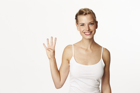 Stunning woman holding up four fingers, portrait