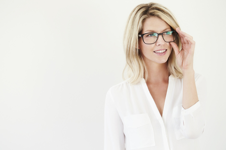 Beautiful woman adjusting glasses in white studio