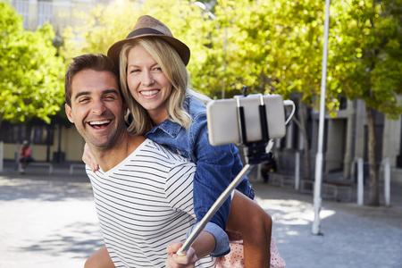 Happy fun couple taking selfie in city