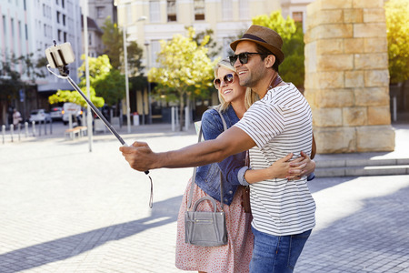 Couple using selfie stick in city, smiling