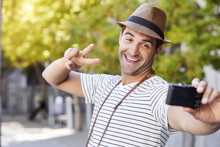 Selfie guy giving peace sign to camera