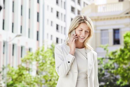 Businesswoman on call in city, smiling Standard-Bild
