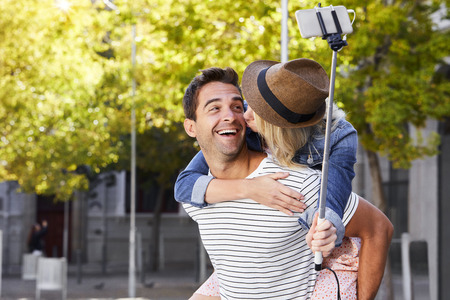 Kissing selfie couple in city, smiling