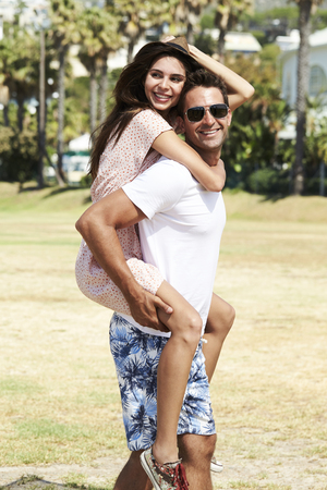 Dude carrying girlfriend in park, smiling